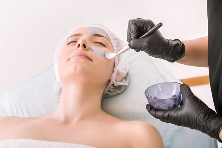 Process of applying a silver cosmetic mask with brush to female client head skin, on a white background. Concept of facial cosmetic treatments at the spa. 版權商用圖片