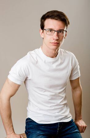A young man in everyday monotonous clothes sits on a white background and confidently looks straight into the camera with a serious expression on his face.