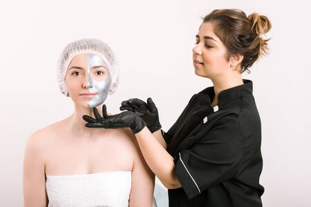 Izolated from white background cosmetologist in gloved hands gently touch with a fingers silver medical beauty mask on woman's face with shiny skin. Concept of spa , skin care and rejuvenation. Imagens