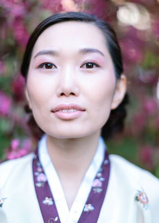 Vertical portrait of beautiful young adult girl with clean skin and delicate make-up, dressed in a traditional folk costume and looking straight into camera. Concept of Eastern beauty and femininity.