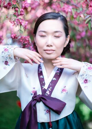 vertical portrait of a beautiful Korean woman in national hanbok costume with closed eyes poses for the camera, bringing her hands to the face against blooming cherry tree background Imagens