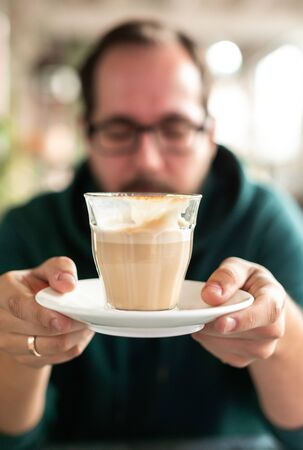 Vertical frame with real male person withclosed eyes holds in front of his face aucer with cup of coffee from which several sips were made. Mental health and self care, resilience concept Imagens