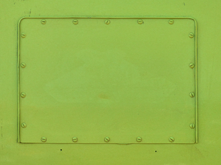 Metal surface with frame and screw heads. Green plain surface with empty space for text. Industrial background. Stock Photo