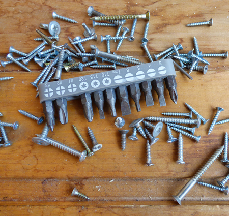 Screws, screwdriver and set of bits (heads) on wood background. Home improvement tools and fasteners. Selected focus on bits. Stock Photo