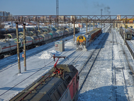 Snow removal train clears railway at the station. Lot of cargo cars and oil tanks at the back. Locomotive moving towards. Sunny winter day somewhere in Siberia.
