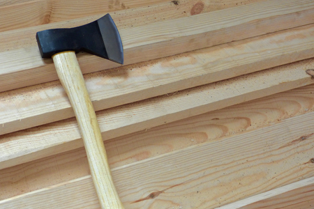 Big sharp ax with black blade and light yellow handle on fresh wooden boards. Wood chopping, construction background with equipment.