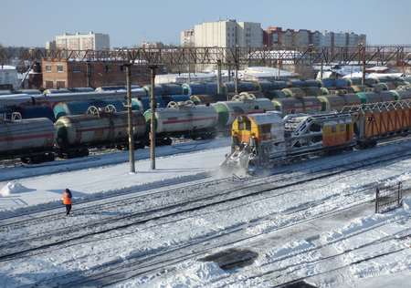 Snow removal train clears railway at the station. Lot of cargo cars and oil tanks at the back. Sunny winter day somewhere in Siberia.