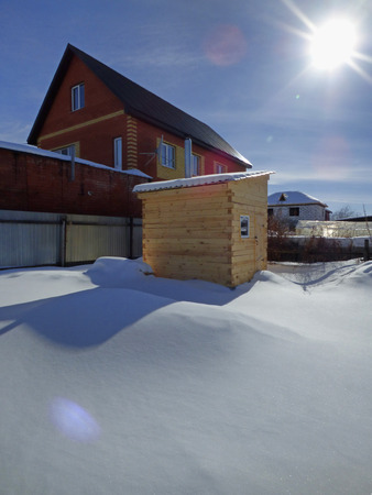 New sauna (banya, russian bathhouse) standing among white snow. Cottage at the back. Summer winter day. With empty space for text.