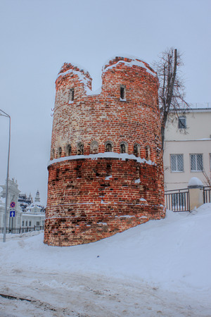 Damaged ancient tower in modern city. Old red brick building among snow. Cloudy winter day. Stock Photo