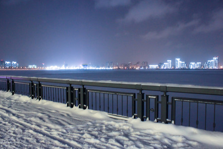 Winter night shot of embankment. Lot of snow on the ground and black metal fence. Cityscape with bright blurred lights on horizon. No people. Stock Photo