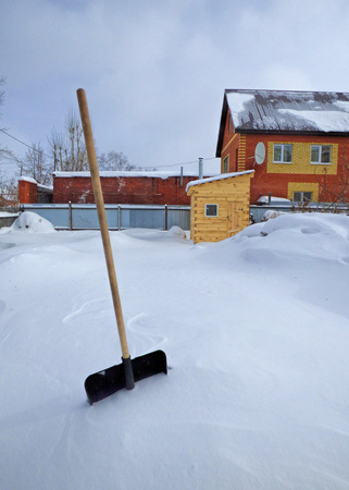 Plastic shovel in the snowdrift. Large territory covered by snow, some buildings at the back. Sunny winter day. Stok Fotoğraf