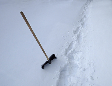 Plastic shovel in the snowdrift. Large territory covered by snow, deep footsteps on white surface. Sunny winter day.
