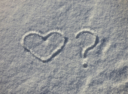 Heart and question symbols on the snow. Romantic sign silhouette on winter ground. Valentines day natural background. Love and doubts.