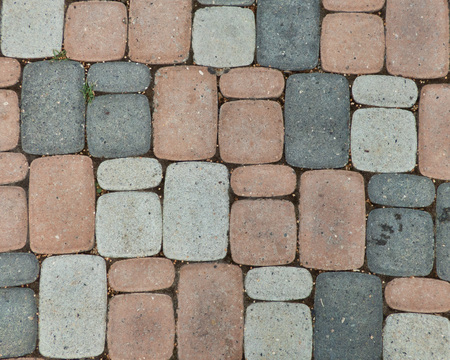Colored tiles on the road. Real stone pavement surface with geometric structure. Rectangular elements arranged in horizontal and vertical lines.