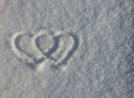 Two heart symbols on the snow. Romantic sign silhouette on winter ground. Valentines day natural background. Stok Fotoğraf