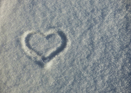 Heart symbol on the snow. Romantic sign silhouette on winter ground. Valentines day natural background.