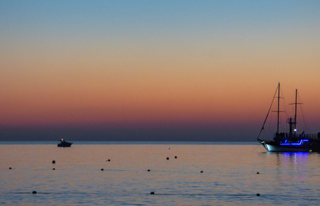 Summer evening on sea coast. Ship silhouette against sky. Natural background.