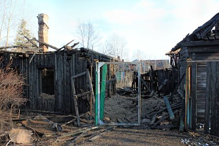 After fire - burnt house. Black burned wooden walls, lot of damaged boards Imagens