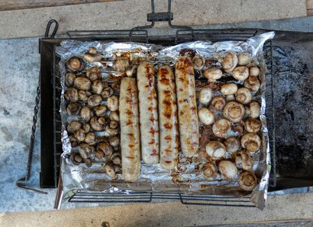 Barbecue sausages and mushrooms grilled on a fire grill. Cooking concept.