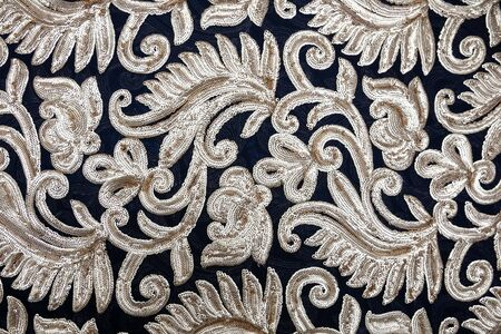 Blue fabric with patterns of silver beads in the form of flowers and branches with leaves spread out on the table. Material