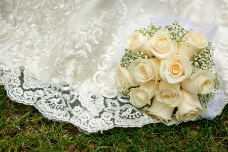 Wedding bouquet of white roses lying on a white wedding dress. Reklamní fotografie