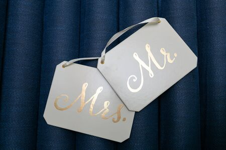 White square plaques with white ribbons and Golden inscriptions Mr and Mrs isolated on blue background.