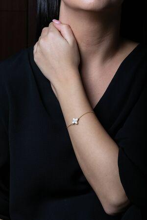 Goldenes Armband an Hand mit Steinen in Form von Blumen auf schwarzem Hintergrund.