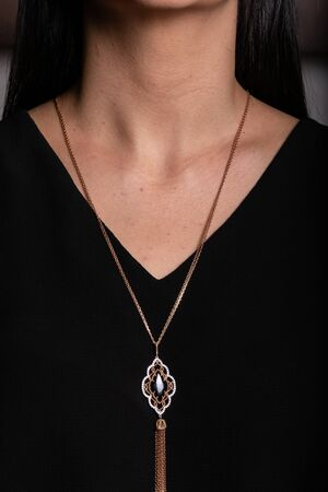 Women chain of rose gold with a pendant  with a black stone in the middle, with egging hanging around his neck.