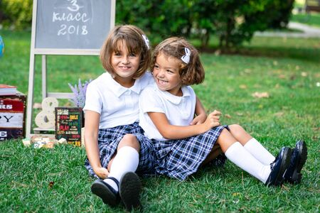 Sentado en la hierba en brazos de niños con camisetas blancas y faldas a cuadros. Foto de archivo