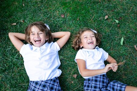 Girls in white t-shirts and plaid skirts lying on their backs on the grass.