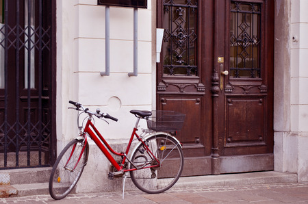 leaning against: red bicycle leaning against a build Stock Photo