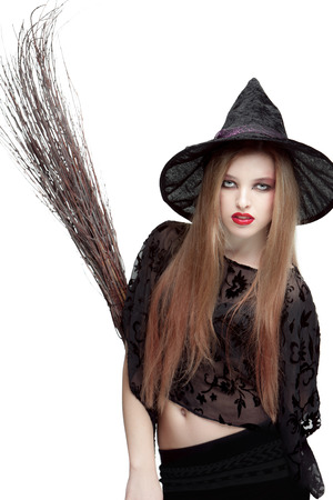 showy: Showy young woman in black witch costume with a broom isolated on white background. Halloween
