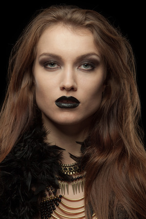 femme fatale: Closeup portrait of a gothic femme fatale with black lips on black background Stock Photo