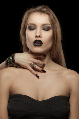 Gothic woman close your eyes with hand of vampire on her neck on black background. Halloween photo