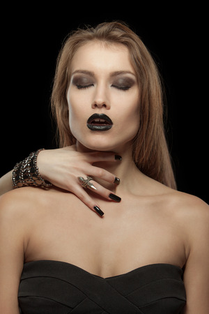 close your eyes: Gothic woman close your eyes with hand of vampire on her neck on black background