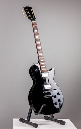 Electric guitar on a stand isolated over ghray background photo