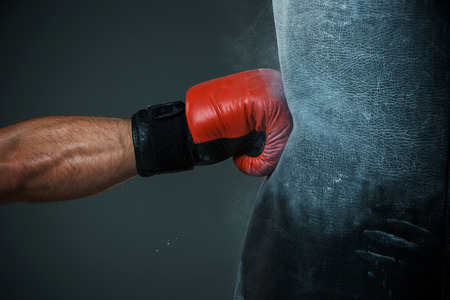 boxing sport: Hand  of boxer and punching bag over black background Stock Photo