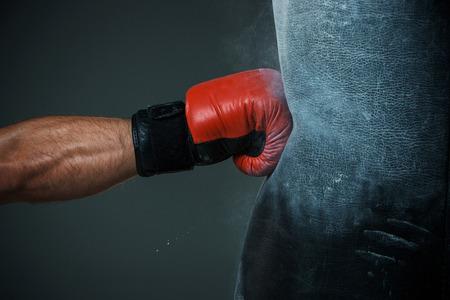 Hand of Boxer und Boxsack auf schwarzem Hintergrund