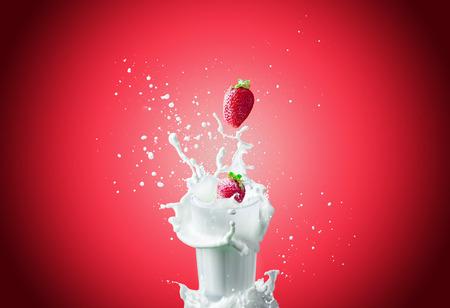 leche: Vista de la bonita rojo fresa fresca caer en el vaso de leche haciendo un chapoteo grande en un fondo rojo