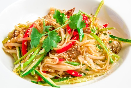 Pan-Asian rice noodles with beef, vegetables, bean sprouts in a sweet and sour sauce on white plate photo