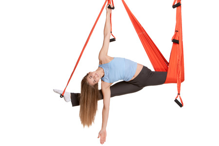asanas: Young woman upside down doing anti-gravity aerial yoga in hammock on a seamless white background. Stock Photo