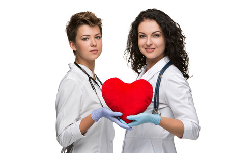 Two doctors holding a red heart, isolated on white background photo