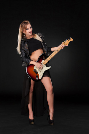 Beautiful blonde girl playing guitar in rock style on a black background photo