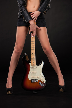Beautiful young girls legs and hands with electric guitar on a black background.