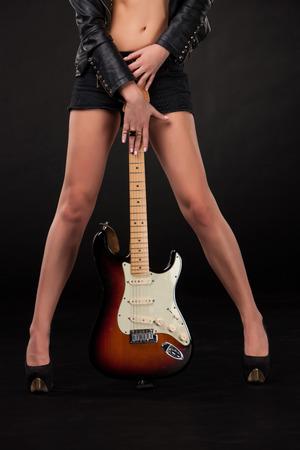 Schöne junge Mädchen die Beine und Hände mit E-Gitarre auf einem schwarzen Hintergrund.