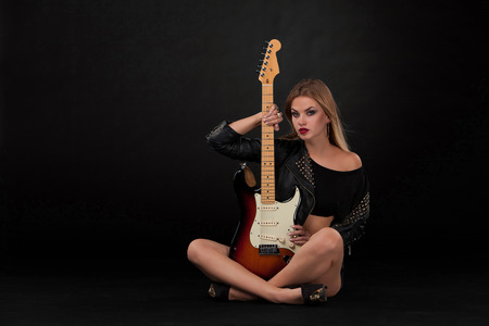 Beautiful blonde girl and guitar in rock style on a black background photo