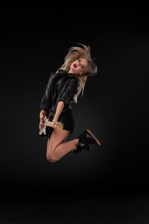 Beautiful jumping blonde girl playing guitar in rock style on a black background photo