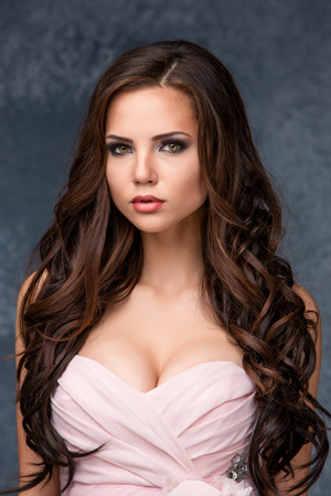 Sexy young brunette woman with her hair posing in a pink dress in studio on gray background Stock Photo