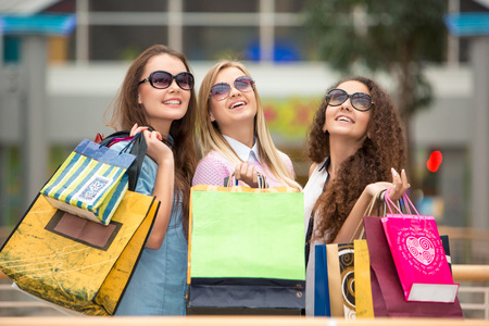jointly: shopping, sale, happy people and tourism concept - three beautiful girls in sunglasses with shopping bags in mall