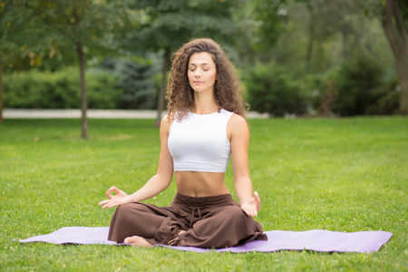 sport and leisure: Pretty woman doing yoga exercises in outdoor park, green grass background Stock Photo